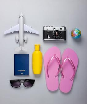 Das konzept eines strandurlaubs. seebad. sommerhintergrund. strand- und reiseaccessoires auf grauem hintergrund. draufsicht. flach liegen
