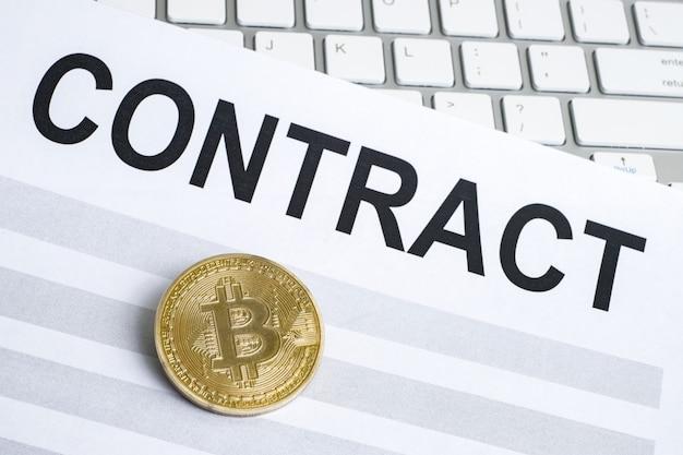 Das konzept eines vertrags mit zahlung in kryptowährung oder bitcoin. bitcoin-münze auf dem vertragsblatt mit der tastatur.