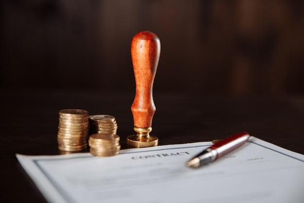 Das konzept von finanzen und wirtschaft. vertrag, stempel, geld und stift auf einem holztisch.