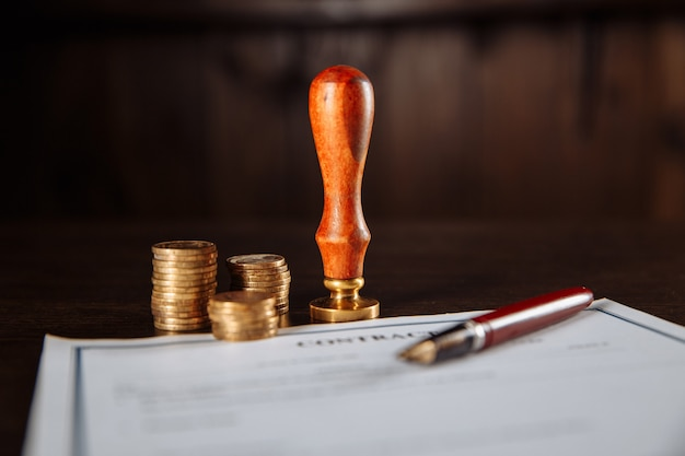 Das konzept von finanzen und wirtschaft. vertrag, stempel, geld und stift auf einem tisch.