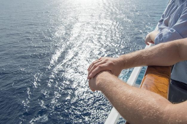 Das konzept von seekreuzfahrten. die hände der männer auf dem geländer des kreuzschiffs auf dem hintergrund