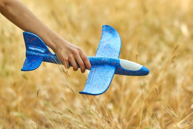 Das konzept von träumen und reisen. glückliches kind, das mit spielzeugflugzeug im sommer auf natur spielt.