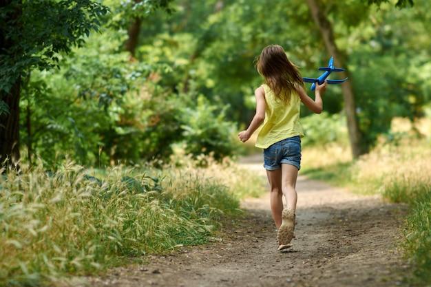 Das konzept von träumen und reisen. glückliches mädchenkind, das mit spielzeugflugzeug im sommer auf natur spielt.