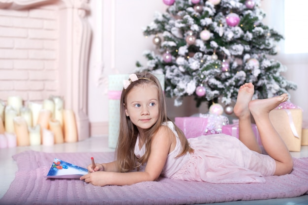 Das konzept von weihnachten, ferien und kindheit. kleines kindermädchen schreibt santa claus einen brief in einem kinderzimmer nahe dem weihnachtsbaum. heiligabend. familientraditionen. winter