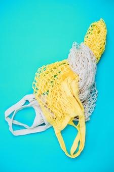 Das konzept von zero waste ohne plastik. wiederverwendbare einkaufstasche aus baumwolle auf blauem hintergrund. handarbeit. auf die natur achten.