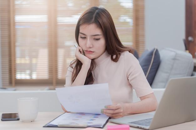 Das konzept, von zu hause aus zu arbeiten, ist eine schöne asiatische frau, die mit einem gesicht arbeitet, das stress und angst zeigt.