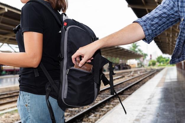 Das konzept, während der reise vorsichtig zu sein: dieb wurde den asiatischen touristen die brieftasche gestohlen, während sie auf ihre karte schaute.