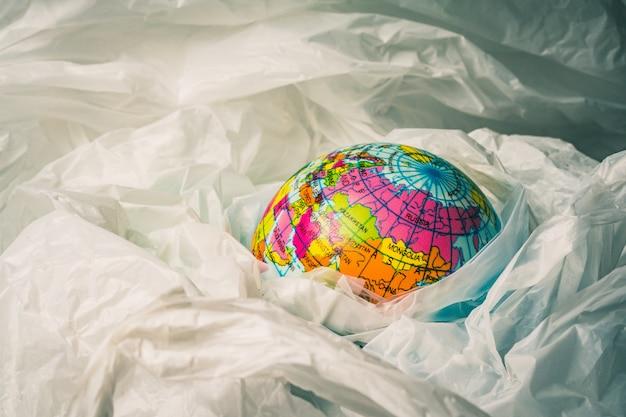 Das konzept zur reduzierung von plastiktüten verwenden: modellierte globen sind in vielen weißen plastiktüten versenkt. plastiktüten sind im begriff, die welt zu überfluten.