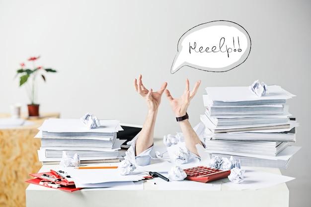 Das konzeptbild oder die collage über viele zerknitterte papiere auf dem schreibtisch eines gestressten männlichen arbeitsplatzes