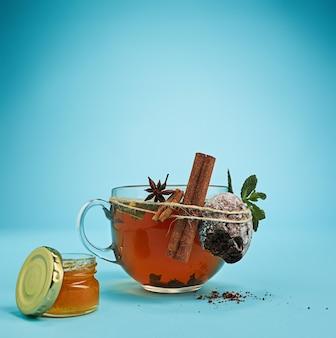 Das konzeptionelle bild einer tasse kräutertee, honig, kuchen auf blauem hintergrund