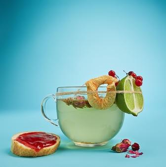 Das konzeptionelle bild einer tasse kräutertee, kuchen, limette auf blauem hintergrund
