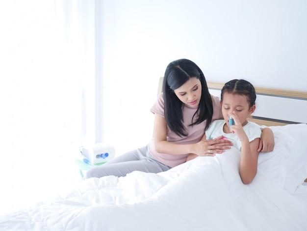Das kranke legen des kleinen asiatischen mädchens, das auf bett im krankenhauszimmer und ihre mutter legt, war mach's gut daneben.