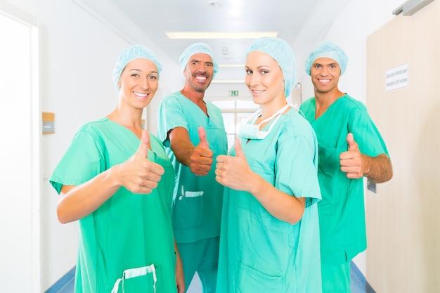Das krankenhaus - das team für medizinische chirurgie ist bereit für die operation. die frauen und männer tragen peelings in einer klinik