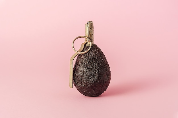 Das kreative konzept der diät. avocado in form einer granate auf rosa hintergrund.