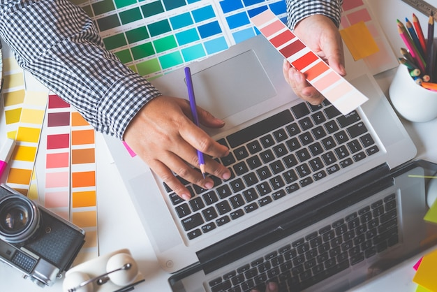 Das kreativteam des grafikdesigners arbeitet derzeit an der gestaltung und farbauswahl an der leitfarbe für die werbegestaltung.