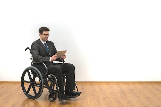 Das lächeln, das im rollstuhl behindert ist, hält ein tablet auf einem weißen wandhintergrund