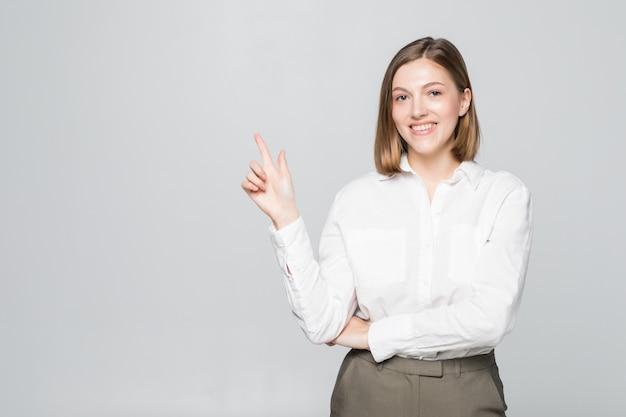 Das lächeln der geschäftsfrau zeigt auf den leeren kopierraum, der über weiß isoliert ist