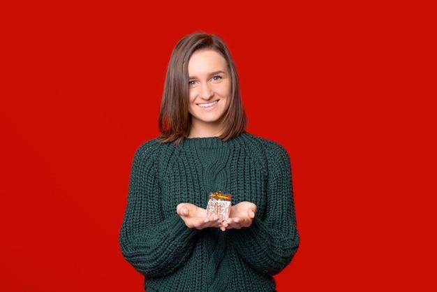 Das lächeln in die kamerafrau hält ein kleines verpacktes geschenk in ihren händen über rotem hintergrund.