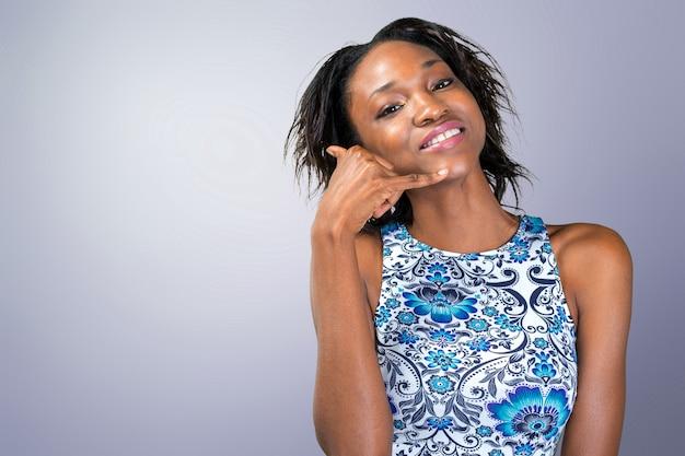 Das lächelnde afrikanische frauenhandeln ruft mich zeichen an
