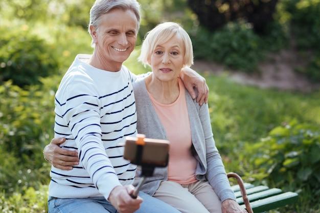 Das lächelnde entzückte alte paar, das sich umarmt und selfie-stock benutzt, während wetter im park genießt und fotos macht