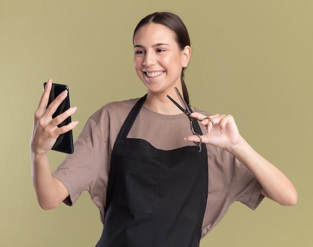 Das lächelnde junge brünette friseurmädchen in der uniform hält eine haarausdünnende schere und schaut auf das telefon auf olivgrün