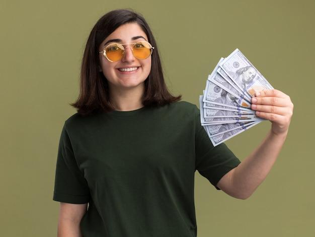 Das lächelnde junge hübsche kaukasische mädchen in der sonnenbrille hält geld auf olivgrün