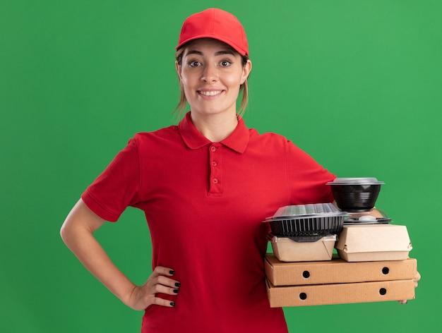 Das lächelnde junge hübsche liefermädchen in der uniform legt die hand auf die taille und hält lebensmittelverpackungen aus papier