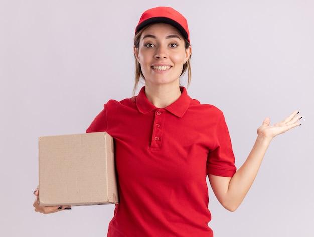 Das lächelnde junge hübsche liefermädchen in uniform hält die hand offen und hält den karton auf weiß