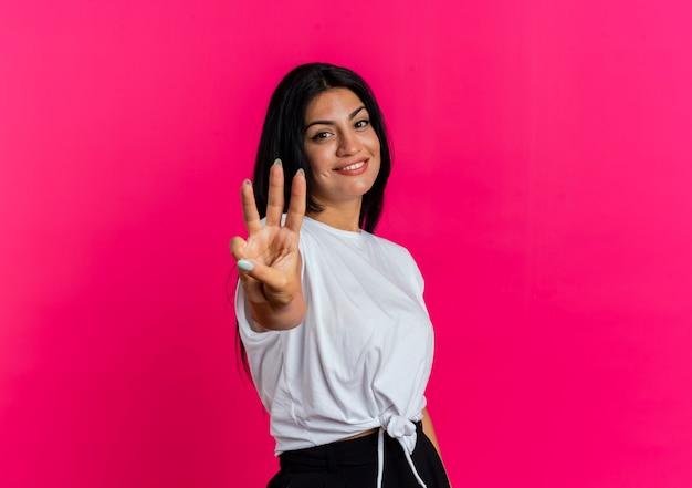 Das lächelnde junge kaukasische mädchen gestikuliert drei mit den fingern