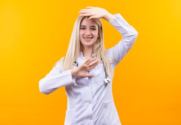 Das lächelnde junge mädchen des doktors, das stethoskop im medizinischen kleid und in der zahnspange trägt, legte ihre hand auf anderen kopf unter kopf auf lokalisiertem gelbem hintergrund