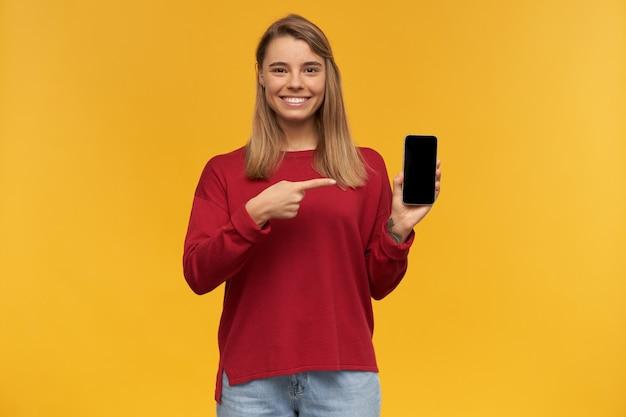 Das lächelnde junge mädchen hält das handy in der hand, der schwarze bildschirm ist auf die kamera gerichtet und zeigt mit dem zeigefinger darauf