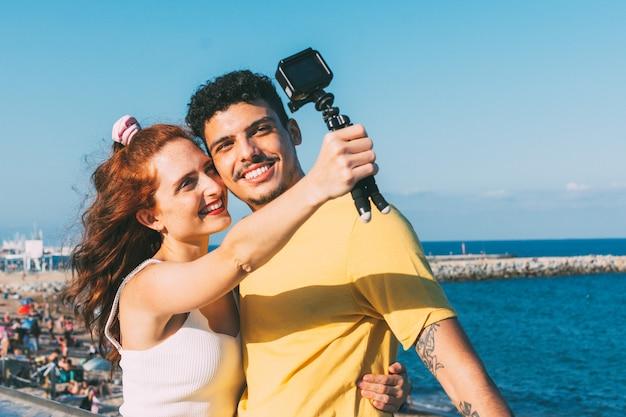 Das lächelnde junge paar macht ein selfie