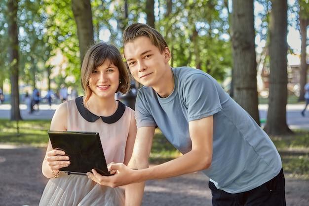 Das lächelnde junge paar schaut sich fotos auf dem tablet-pc an, während es im öffentlichen park spazieren geht.
