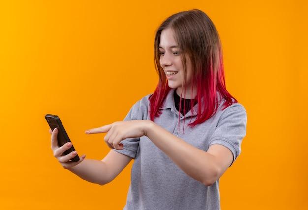 Das lächelnde junge schöne mädchen, das graues t-shirt trägt, zeigt auf telefon in ihrer hand auf lokalisiertem gelbem hintergrund