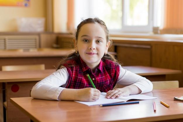 Das lächelnde kaukasische mädchen, das am schreibtisch im klassenzimmer sitzt und bereiten vor, um zu studieren.
