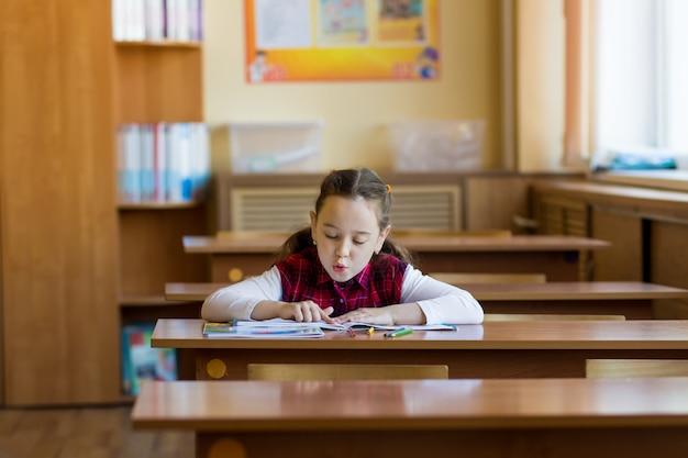 Das lächelnde kaukasische mädchen, das am schreibtisch im klassenzimmer sitzt und liest sorgfältig das lehrbuch.