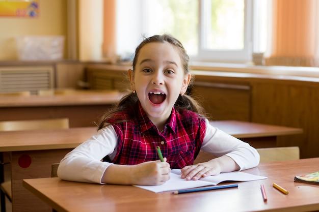 Das lächelnde kaukasische mädchen, das am schreibtisch im klassenzimmer sitzt und schreit glücklich.