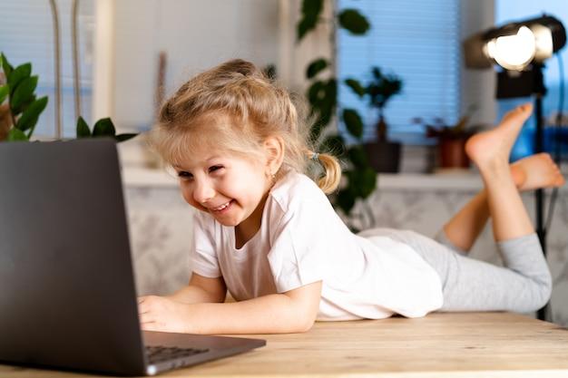 Das lächelnde kleine kaukasische mädchen hat eine videoanruffernbedienung.