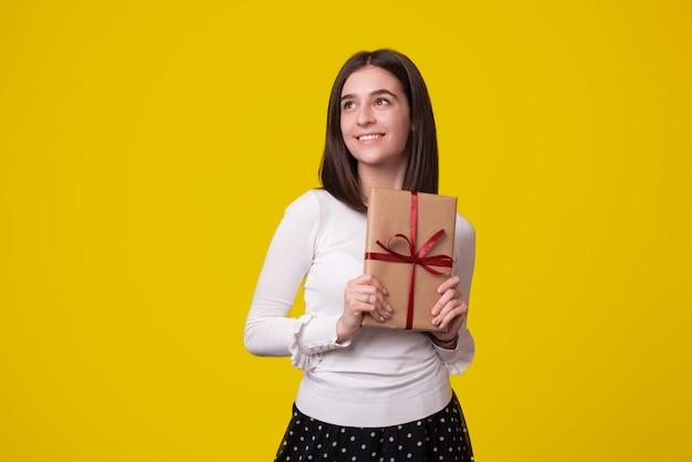 Das lächelnde mädchen, das ein geschenk hält, träumt von etwas großem auf gelbem hintergrund.