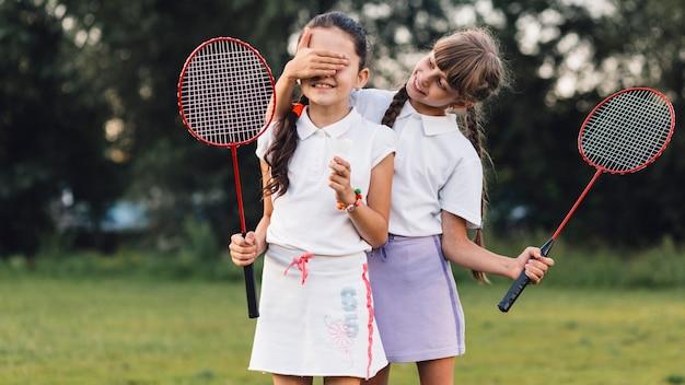 Das lächelnde mädchen, das ihre freundin bedeckt, mustert, badminton halten