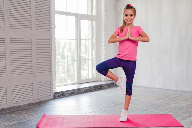 Das lächelnde mädchen, das im yoga steht, werfen auf einem bein auf