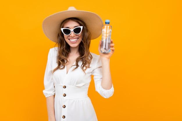 Das lächelnde mädchen, das in einem kleid und in einer sonnenbrille mit einem hut gekleidet wird, hält eine flasche wasser über gelbem hintergrund