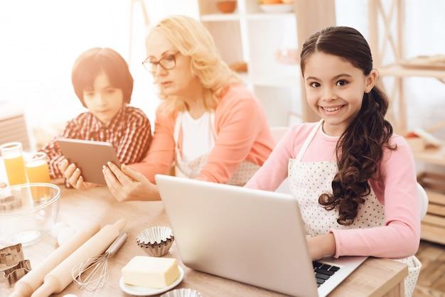 Das lächelnde mädchen, das laptop in der küche verwendet, backen konzept