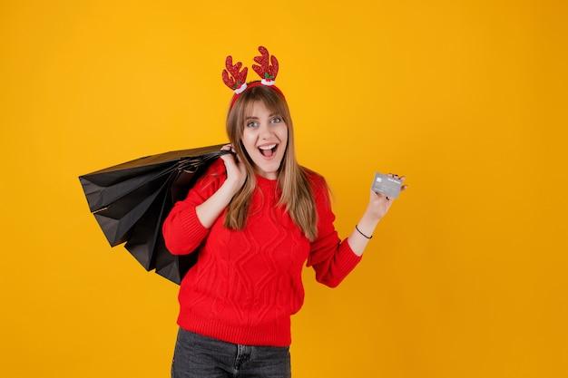 Das lächelnde mädchen, das schablonenkreditkarte und ferieneinkaufsgeschenk hält, bauscht sich das tragen des lustigen bands