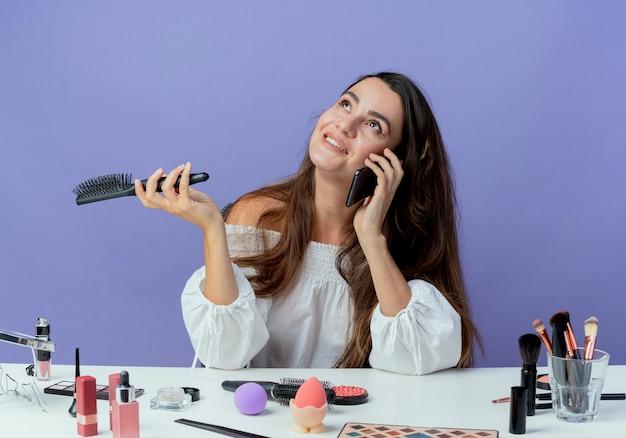 Das lächelnde schöne mädchen sitzt am tisch mit make-up-werkzeugen und hält den haarkamm, der am telefon spricht und isoliert auf lila wand schaut