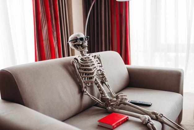 Das lächelnde skelett in der brille sitzt auf der couch zwischen buch- und fernsehfernbedienung, fenster und roten vorhängen