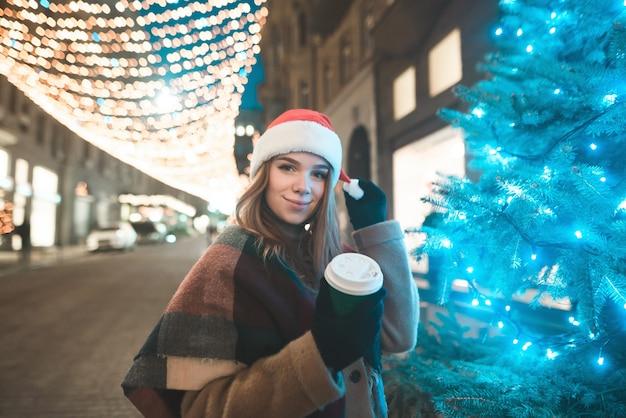 Das lächelnde süße mädchen in einer weihnachtsmütze und einer tasse kaffee in ihren händen steht am weihnachtsbaum auf der straße