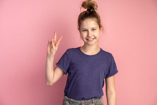 Das lächelnde teenager-mädchen zeigt eine geste des sieges