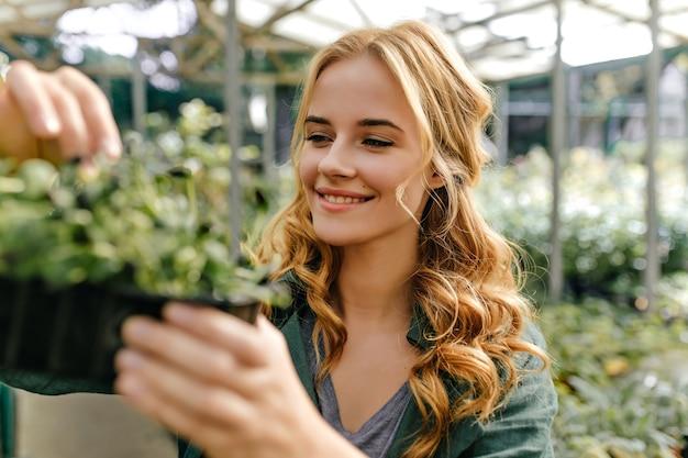 Das langhaarige rothaarige mädchen ist glücklich und lächelt aufrichtig und hält einen topf mit grün in ihren händen. nahaufnahmeporträt außerhalb von pflanzen umgeben.