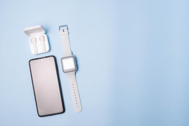 Das layout der uhr und des telefons auf blauem hintergrund. geräte und elektronik.